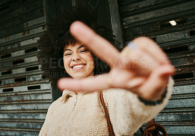 Buy stock photo Shot of a young woman showing the peace sign while out in the city