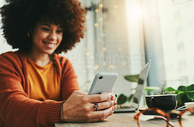 Buy stock photo Shot of a young woman using her smartphone in a coffee shop