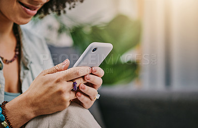 Buy stock photo Cropped shot of an unrecognisable woman sitting alone on her sofa at home and using her cellphone