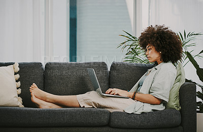 Buy stock photo Full length shot of an attractive young woman sitting alone on her sofa at home and using her laptop