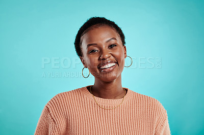 Buy stock photo Shot of a young woman smiling while standing against a turquoise background