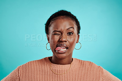 Buy stock photo Shot of a young woman pulling a face while standing against a turquoise background