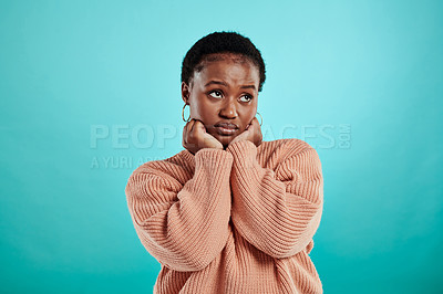 Buy stock photo Shot of a beautiful young woman sulking while standing against a turquoise background