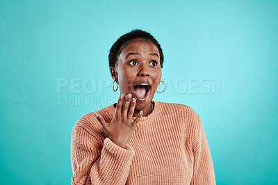 Buy stock photo Shot of a young woman looking surprised while standing against a turquoise background