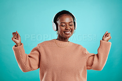 Buy stock photo Shot of a woman wearing headphones while standing against a turquoise background