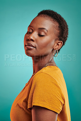 Buy stock photo Shot of a beautiful young woman posing against a turquoise background