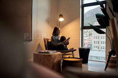 Buy stock photo Shot of a young woman using her smartphone to send a text message