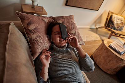 Buy stock photo Shot of a young woman lying on the couch after her phone fell on her face