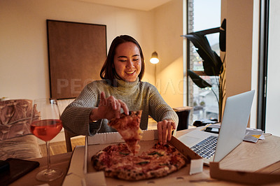 Buy stock photo Shot of a young woman having pizza while working from home