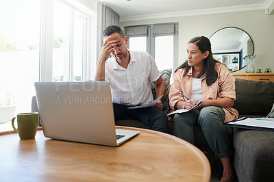 Buy stock photo Shot of a young couple sitting on the sofa at home together and feeling stressed while calculating their finances