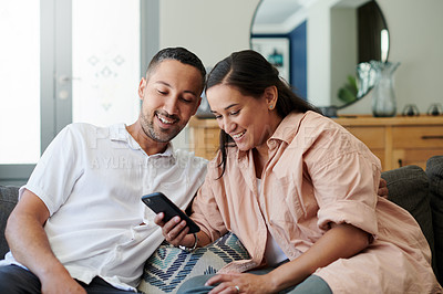 Buy stock photo Shot of a young couple sitting on the sofa at home together and using a cellphone