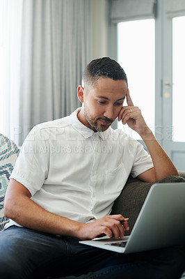 Buy stock photo Shot of a handsome young man sitting alone on his sofa at home and looking contemplative while working from home