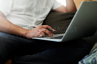 Buy stock photo Cropped shot of an unrecognizable man sitting alone on his sofa at home and using his laptop to work from home