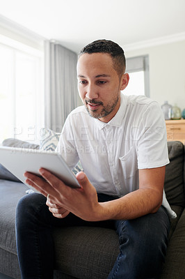 Buy stock photo Shot of a young man sitting on his sofa at home and using a digital tablet to work from home