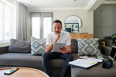 Buy stock photo Shot of a young man sitting on his sofa at home and looking contemplative while using a digital tablet