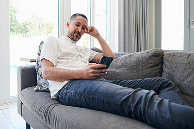 Buy stock photo Shot of a handsome young man sitting on his sofa at home and looking contemplative while using his cellphone