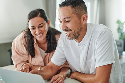 Buy stock photo Shot of a young couple sitting together and using a laptop to work from home