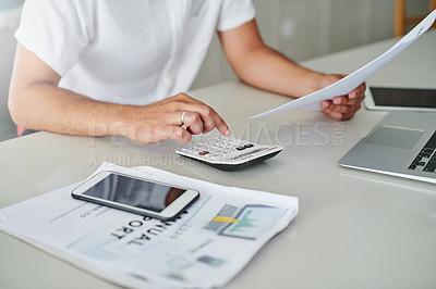 Buy stock photo Cropped shot of an unrecognizable man sitting alone at home and calculating his finances