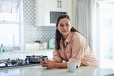 Buy stock photo Shot of an attractive young woman leaning on her kitchen counter at home and looking contemplative while using her cellphone