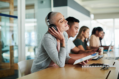Buy stock photo Cropped shot of an attractive young businesswoman listening to music while sitting in the boardroom with her colleagues