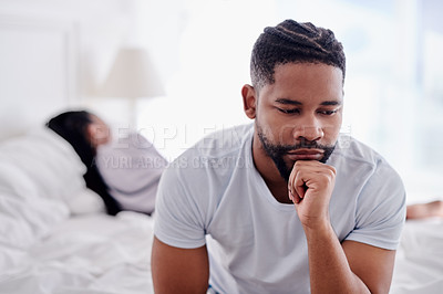Buy stock photo Shot of a young man sitting on the bed at home and looking stressed while his girlfriend sleeps behind him