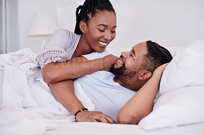Buy stock photo Shot of a young couple lying on their bed at home and enjoying a romantic moment together