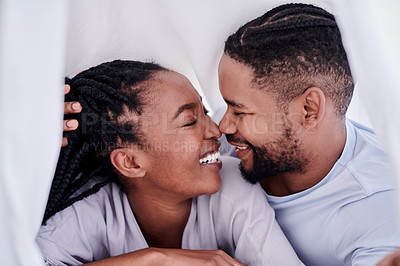 Buy stock photo Shot of a young couple lying on their bed at home together and bonding during the day