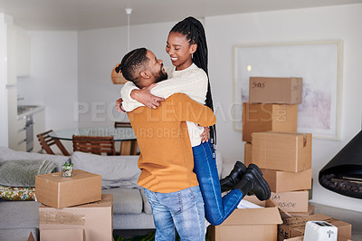 Buy stock photo Shot of a young couple embracing in their new home