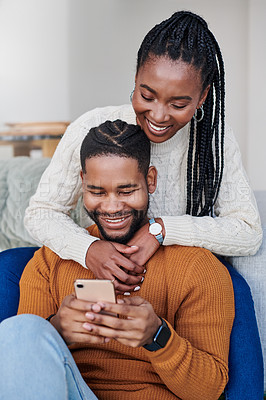 Buy stock photo Shot of a young couple using a cellphone while relaxing together at home