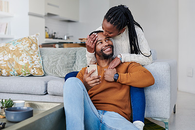 Buy stock photo Shot of a young woman kissing her boyfriend on the forehead while relaxing together at home