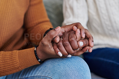 Buy stock photo Closeup shot of an unrecognisable couple holding hands while relaxing together at home