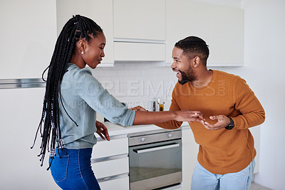 Buy stock photo Shot of a young couple dancing and having fun together in the kitchen at home