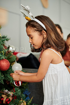 Buy stock photo Cropped shot of an adorable little girl decorating her family Christmas tree in the living room at home