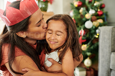 Buy stock photo Cropped shot of an adorable little girl being kissed by her mother on Christmas morning