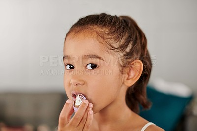 Buy stock photo Shot of a young girl eating easter eggs at home