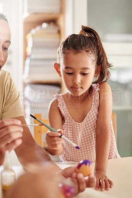 Buy stock photo Shot of a young girl painting eggs at home