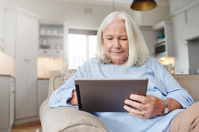 Buy stock photo Shot of a senior woman using a digital tablet at home