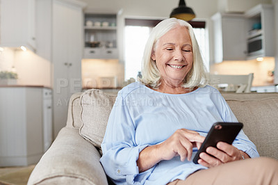 Buy stock photo Shot of a senior woman using a cellphone at home
