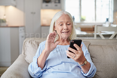 Buy stock photo Shot of a senior woman having a video chat on a cellphone at home