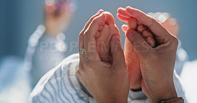 Buy stock photo Shot of an unrecognisable woman holding her baby's feet on the bed at home