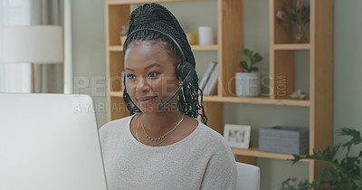 Buy stock photo Shot of a young female call centre agent using a computer while working from home