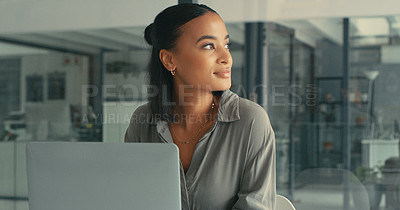 Buy stock photo Shot of a beautiful young woman lost in thought while using her laptop in a modern office