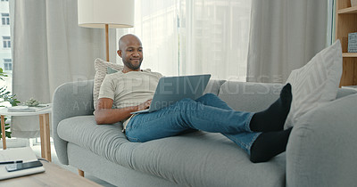 Buy stock photo Shot of a young man using a laptop while sitting on the couch at home