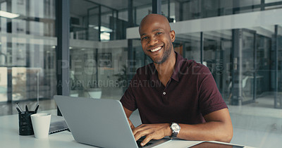 Buy stock photo Portrait of a happy young man using his laptop while working in a modern office