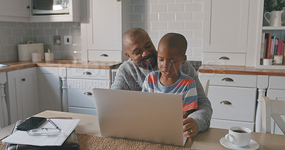 Buy stock photo Shot of a mature man and his grandson using a laptop at home