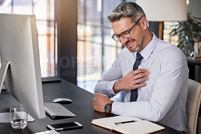 Buy stock photo Shot of a businessman holding his chest in pain while seated at his desk