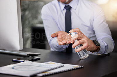 Buy stock photo Shot of a businessman sanitising his hands while sitting at his desk