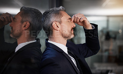 Buy stock photo Shot of a businessman looking stressed while standing in his office