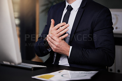 Buy stock photo Shot of a businessman experiencing discomfort in his hands while working at his desk