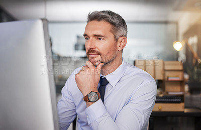 Buy stock photo Shot of a businessman looking thoughtful while sitting at his desk